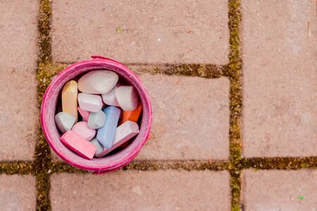 A bucket of colorful chalk on the asphalt in plastic box. Drawing with chalk on the pavement.multicolored crayons for drawing.