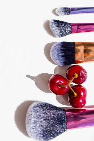 Set of various natural bristle makeup brushes and berry: for applying foundation powder blush eyeshadow eyebrow brushes and others. Professional tools of make-up artist .Copy space. Beauty concept Stock Photo