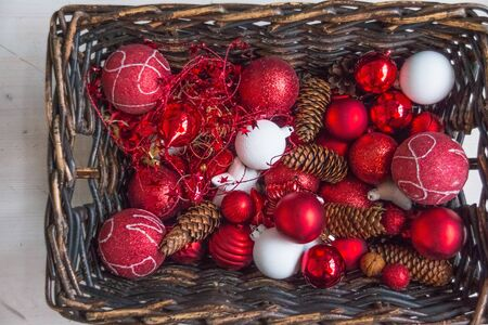 Christmas basket with decor, gifts with red satin ribbon, candy canes, pine cones, red and white garlands on white wooden background. Happy new year, holidays concept Stockfoto