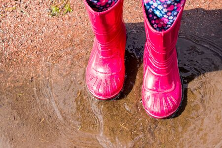 legs of child in orange rubber boots jumping in the autumn puddles. kids bright rubber boots,gardening. Rainy day fashion.Garden Rainy Rubber Shoes. boots for rainy day. Autumn kids boots concept.
