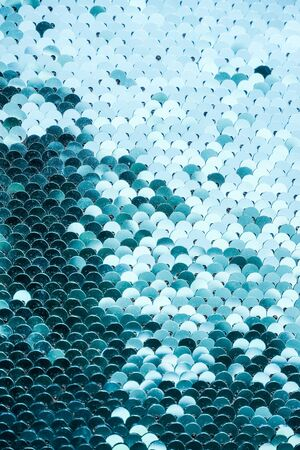 Abstract blue Texture with bright Sequins . Glamor scales Background with shiny Sequins on fabric. Beautiful Holiday Wallpaper with pattern of round Sequins.textile texture. Good for disco, party. Stockfoto