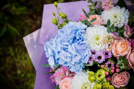 beautiful blossoming flower bouquet of fresh hydrangea, roses, eustoma, mattiola, flowers in blue, pink and white colors. rich bouquet with blue hydrangea, with water drops. Happy holidays gift. Stockfoto