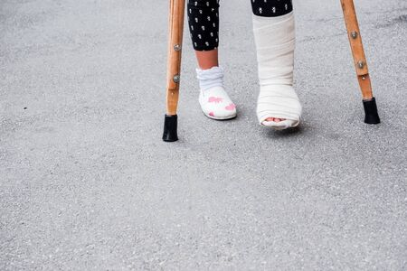 Young girl in orthopedic cast on crutches walking on the street near the road. Child with a broken leg on crutches, ankle injury. Bone fracture and ankle fracture in children