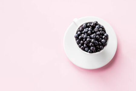 Ripe blueberries in Cup on pstel background. beautiful summer harvest season concept. Fresh blueberries. Top view.Copy space.Summer and healthy food concept.