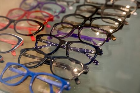 exhibitor of glasses consisting of shelves of fashionable glasses shown on a wall at the optical shop. Colorful Elegant eyeglasses in a store.Selective focus