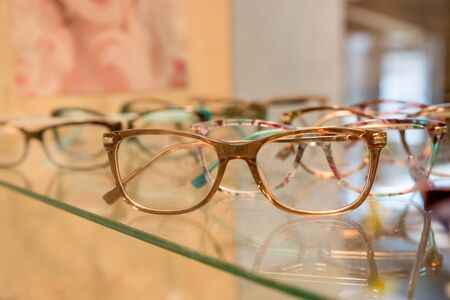 optics, health care and vision concept - close up of eyeglasses at optician.exhibitor of glasses consisting of shelves of fashionable glasses shown on a wall at the optical shop.Selective focus