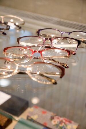 Many glasses rows at optical retail store. Rich assortment choice of different eyewear frames on eyeglasses shop display.optical shop.Row with colorful modern eyeglasses.Selective focus.