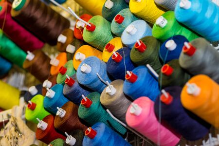 sewing threads in many different colors on a performed metal wall. Sewing workshop. Sewing tools. Tailor shop theme background, Textiles and clothing industry concept. selective focus.