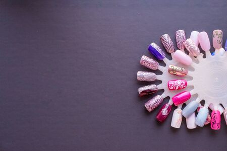 Nail color samples in different colors. Big collection of artificial finger nails painted in different coolors. Nail beauty salon.Colorful nail lacquer manicure swatches. Top view of nail art wheel palette.