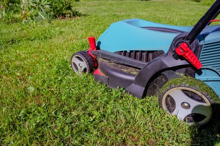 Lawn mower on green grass. mower cutting fresh grass in backyard, garden service.equipment, mowing, gardener, care, work, tool.Copy space Zdjęcie Seryjne - 128906938