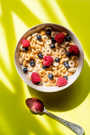 Healthy breakfast with berries,dried fruits, nuts, cereals top view copy space.cornflakes with raspberries and blueberries on yellow background.Sweet cornflakes with berries and milk as healthy meal