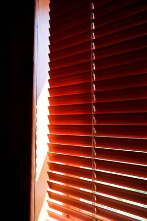 Closed orange plastic blinds with sunlight in the morning. window with blinds. Interior design of living room with window horizontal blinds. Window with Sun-protection jalousie Stockfoto