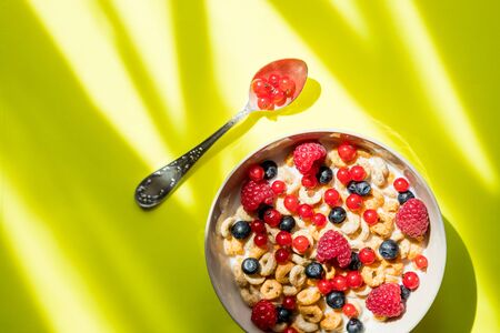 Healthy breakfast with berries,dried fruits, nuts, cereals top view copy space.cornflakes with raspberries and blueberries on yellow background.Sweet cornflakes with berries and milk as healthy meal 写真素材 - 128907028