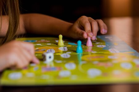Multi-colored game chips with dice on the playing board. Board game.children sit in kindergarten at the table engaged, learn in the nursery,Playing table game.