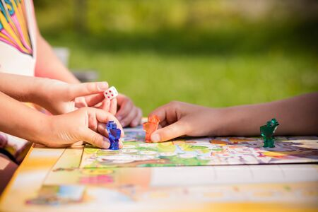 Board game and kids leisure concept. Kids are playing. people holding figures in hand. yellow, blue, green and red wood chips in children play.concept of board games. Dice, chips and cards. Party games Zdjęcie Seryjne - 128907083