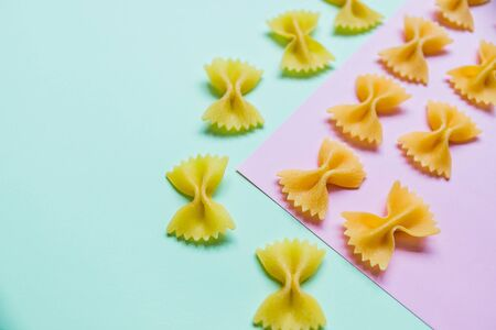 Italian pasta pattern on pastel colors background. Various colors of bow tie farfalle pasta. Top view. Repetition.Italian Macaroni Pasta raw food background or texture.Traditional pasta.Menu concept