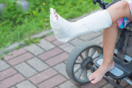 Close up photo of child on wheel chair with cast. Selective focus .copy space. The wheelchair for disability person.child with cast around broken leg in garden.accident concept. Banque d'images - 128907246