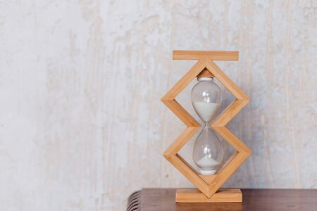 Close up of hourglass clock on a wooden floor with copy space. Hourglass time passing concept for business deadline, urgency and running out of time.Time abstraction.wooden Hourglass.Copy space