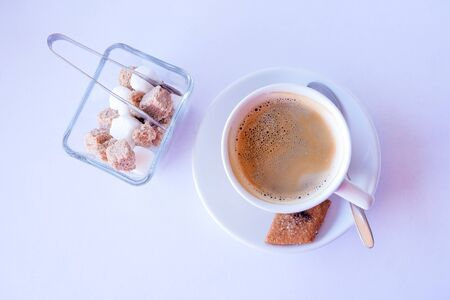 Cup of coffee with brown and white sugar on a white table.Bowl with white and brown sugar cubes and tongs. Hot drink for good morning. Copy space 写真素材 - 128907301