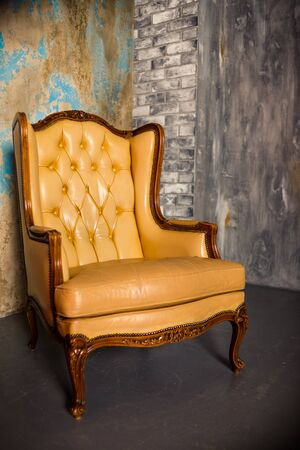 Luxury wooden chair with beige leather. Antique armchair isolated on concrete background.elegant design.classic royal luxury style Zdjęcie Seryjne