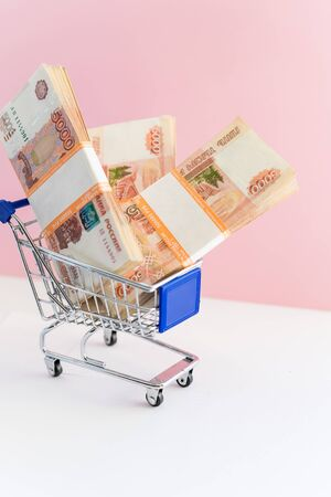 Shopping for the Best Deal. Shopping cart filled with twenties, fives, and singles. Concept of shopping for the best deal before buying.