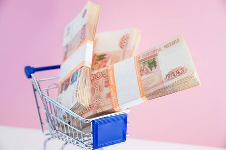 Shopping cart filled with twenties, fives, and singles. Concept of shopping for the best deal before buying. 版權商用圖片