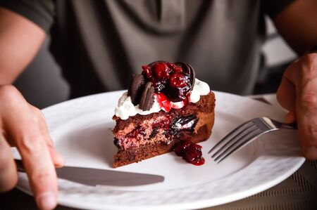 food, junk-food, culinary, baking and holidays concept - close up of male hands eating chocolate cherry cake with fork and sitting at wooden table.tasty dessert.chocolate cake slice on white plate.