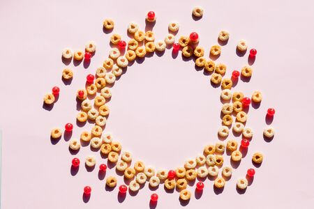 Whole grain cereal rings as circle on soft pink background. Healthy and Delicious breakfast. Top view. Copy space.circle of Breakfast cereal, corn flakes with berries. 스톡 콘텐츠