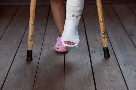 Girl on crutches, leg in cast. patient holding wooden crutches isolated on blurred background. kid after misadventure , insurance concept. difficulties of movement. Copy space 写真素材
