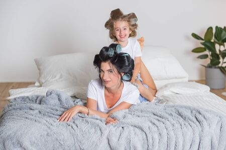 portrait of happy Mother and little daughter in hair curlers.happy mom and daughter having fun on the bed in pajamas.Happy loving family in bedroom in scandinavian style.