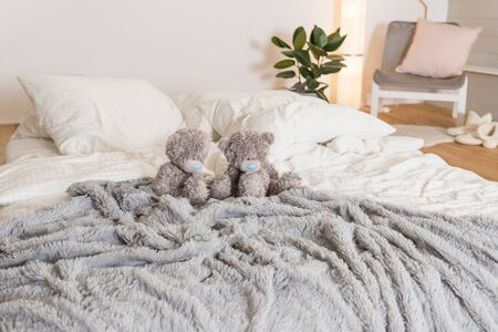 Scandinavian bedroom room with standing lamp, plant, grey wall, white furniture, teddy bears. Cute modern interior and toys.Stylish and bright scandinavian decor.Cosy bedroom with eco decor.
