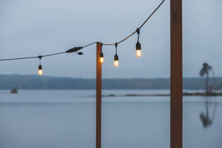 Twilight, gray color sky at the lakescape, electric lamps as garland and wooden terrace, pier. romantic atmosphere of evening. Night cafe terrace. Retro garland for home decor.
