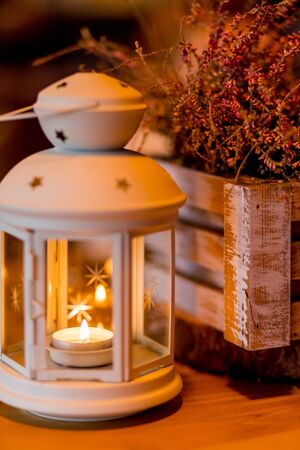 Autumnal decorated terrace.Seasonal home garden autumn decoration with heather flower.White lantern and heath plants in white wooden box.Autumn arrangement with burning candle.Toned image 写真素材