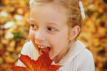 Happy little girl playing with autumn leaves. ute funny girl with open mouth in autumn park.Close up portrait of lovely girl with emotional face fooling and making faces. Smiling and laughing kid.