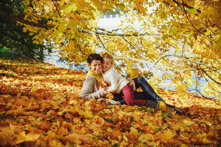 mother playing with her daughter in autumn park. Mom and her child playing together on autumn walk outdoors. Happy loving family having fun.Fashion family concept - stylish mother and child wear. 写真素材