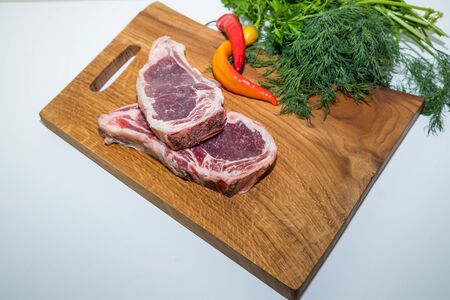 Raw beef steak with rosemary and and red hot pepper and dill on cutting board on white background.raw ribeye steak.Raw fresh Chuck roll steak with herbs and salt on a cutting Board top view. Stock Photo