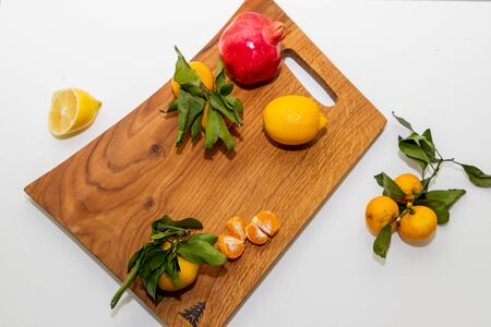 Group of various fruit consists half of tangerines, pomegranates,lemon close up fresh fruit on wooden cutting board, vitamin c from fruit.Organic tropical fruits 写真素材