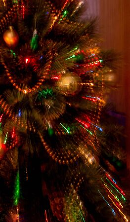 Lights on Christmas tree in focus with two second exposure while zooming to create abstract light streaks.Colorfull decoration light with zoom effect technique. Merry christmas and happy new year 写真素材
