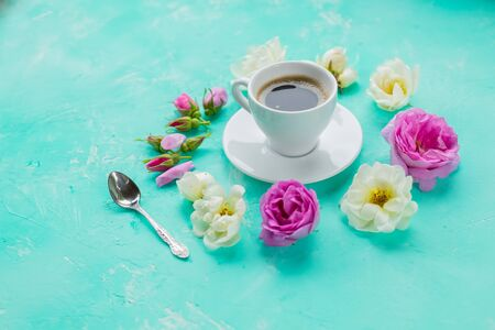 Flat lay composition with spring ranunculus flowers and cup of coffee on color background. Space for text