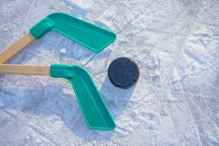 Ice hockey stick and puck on ice.equipment for hockey player in winter game season. Фото со стока