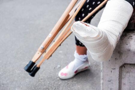 Niña irreconocible sentada en la calle en un banco con una pierna rota y muletas. Niña discapacitada con muletas. Un accidente al saltar en un trampolín. Una fractura de tobillo.