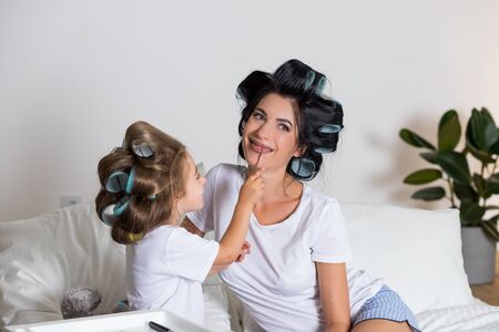 I love my mom.Happy Mothers Day. Beautiful mother with her little cute daughter are having fun at home. Doing makeup to each other and smiling.Family having fun on the bed in pajamas.Mother and daughter in hair curlers Stockfoto