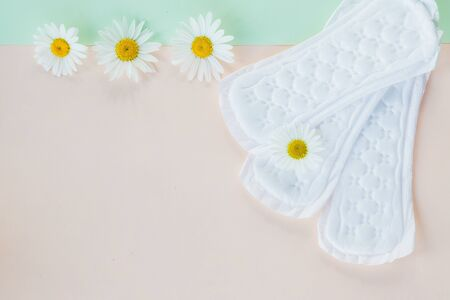 Womans Sanitary Pads and Gerbera Daisy Flower on Pink green Background, Feminine Hygiene Concept.Concept of critical days, menstruation.Copy space.Soft tender protection every day