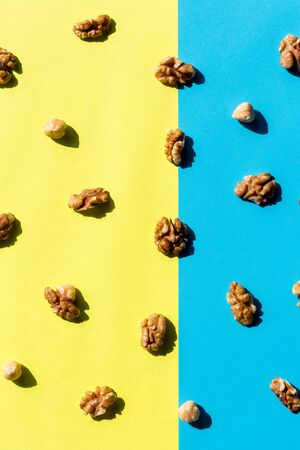 Walnut kernel pattern backdrop. One open nut shell with kernel on yellow blue background. Top view.Flat lay composition with Different types of nuts on colorful background.nut textures and surface with pattern for background