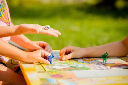 Family playing a board game at home, one kid is on the move and capturing the piece of another player