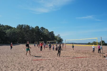 St. Petersburg, Russia, September 10, 2019.Young tourists, people playing volleyball.Beach volleyball sports. Young man kicks the ball. City holiday. Sunny day.Weekend activity concept Редакционное