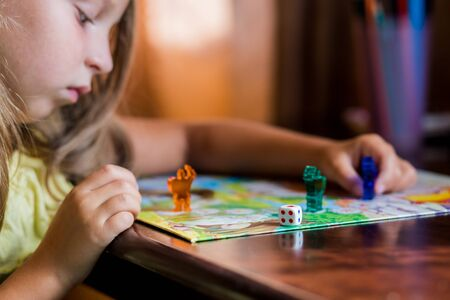 little blonde girl hold blue people figure in hand.colorful play figures with dice on board.Board game and kids leisure concept.Board games for the home. Yellow, green and red plastic chips and dice on Board games for children .