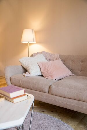 Small coffee table and candles next to designed sofa with pastel colored pillows.Still life details of nordic living room. bright living room interior. elegant sofa in living room with different fabrics cushions and a side table with a stylish lamp Archivio Fotografico - 133362646