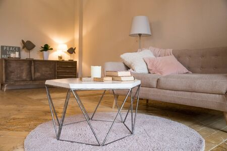 Small coffee table and candles next to designed sofa with pastel colored pillows.Still life details of nordic living room. bright living room interior. elegant sofa in living room with different fabri
