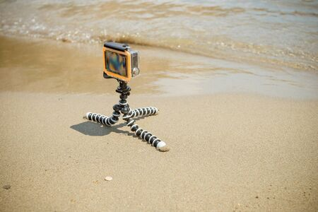 small modern action camera, action camera removes sea view.Action camera mounted on a tripod on a beach recording ocean and waves. camera in waterproof case.Video blogger shoots 4k footage outdoor.